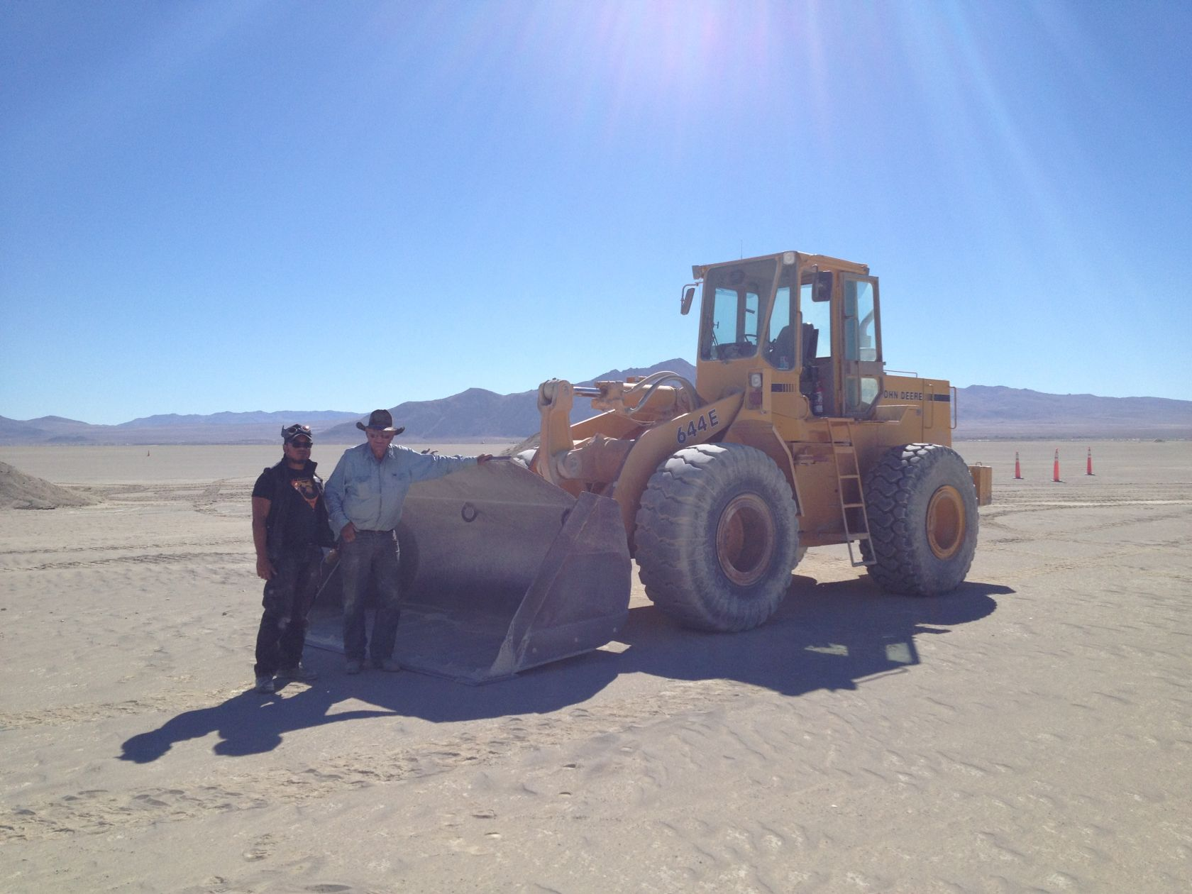 Stuart from Gerlach (standing on the right, with Resto boss D.A.) at the site of the Man Burn removes the decomosed granite that protects the playa surface from burn scarring.