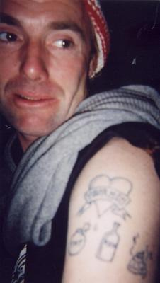 behold: johnny joyce. a man with poop tattooed on his arm and 2 DUM 2 DIE on the inside of his lower lip. he is your god
